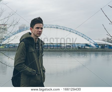 Potrait of the young man on the city river