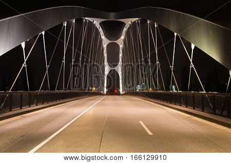 Modern bridge over the river Main lit by lamps at night design movement front view. Frankfurt am Main . Germany.