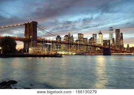 Silhouette of Manhattan skyline with Brooklyn Bridge at sunset.