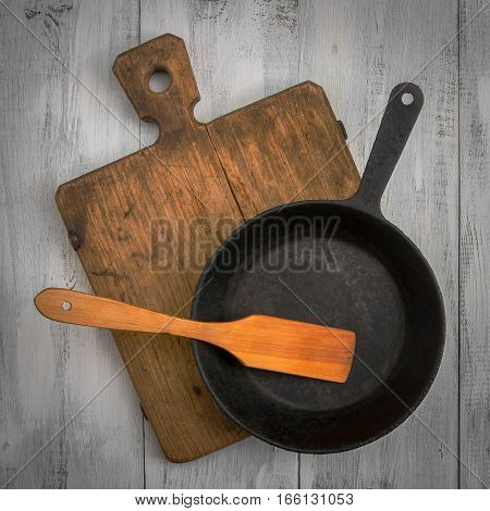 Cutting board pan and wooden shovel lying on the painted kitchen table