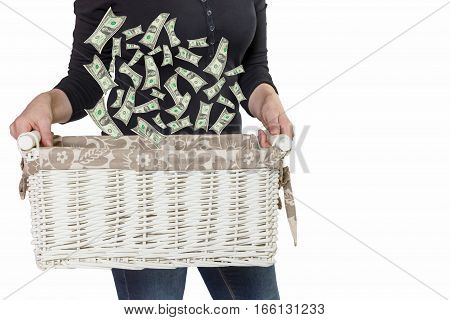 Standing woman is holding white basket where falling US dollar bills. All is isolated on the white background.