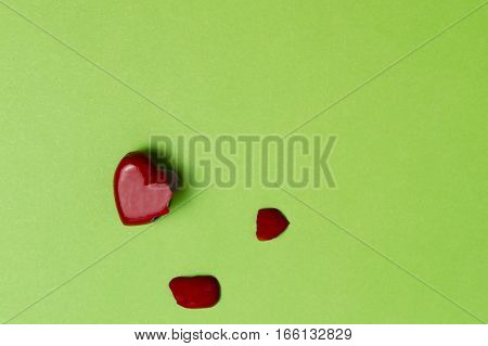 Broken heart on greenery background. Top view