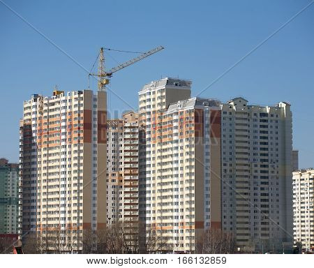 Many new high-rise buildings constructing in process over clear blue cloudless sky horizontal view