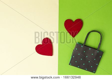 Colourful shopping bag and two red hearts on greenery and yellow colored paper background. Top view. Flat lay. Copy space for text