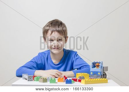 Little kid boy playing with colorful plastic construction bricks at the table