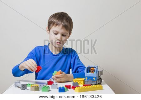 Concentrated focused child sittings and looking at colorful plastic construction toy blocks at the table. Children, toys, leisure concept