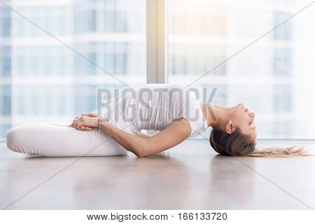 Young attractive woman practicing yoga, stretching in Fish exercise, variation of Matsyasana with lotus legs pose, working out, wearing sportswear, white t-shirt, pants, full length, near floor window