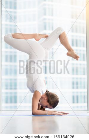 Young woman practicing yoga, standing in variation of Pincha Mayurasana exercise with bent legs, handstand pose, working out, wearing white sportswear, indoor full length, floor window with city view