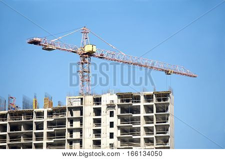 Big hoisting tower crane over top of construction building under cloudless sky