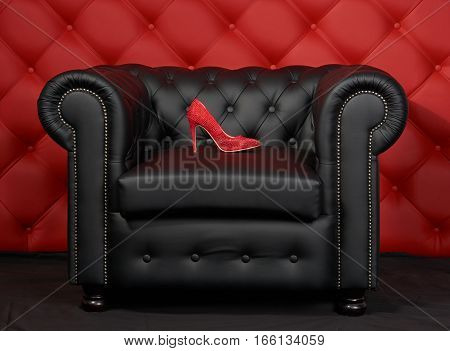 Pair of red women's shoes with rhinestone on black leather armchair. Red leather carriage upholstery on the background.