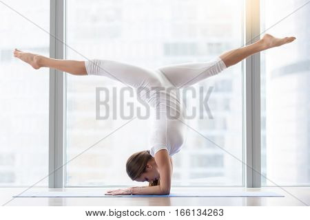 Young woman practicing yoga, standing in handstand exercise, Pincha Mayurasana pose, working out, wearing sportswear, white t-shirt, pants, indoor full length, near floor window with urban view