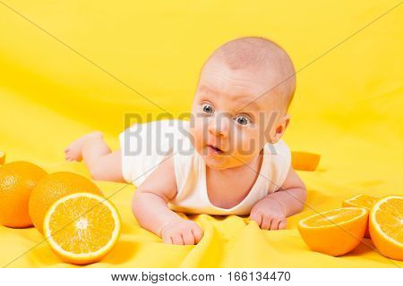baby boy lies on a yellow with oranges many