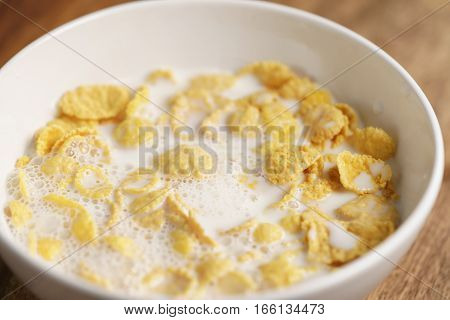 corn flakes with milk in white bowl, simple healthy breakfast