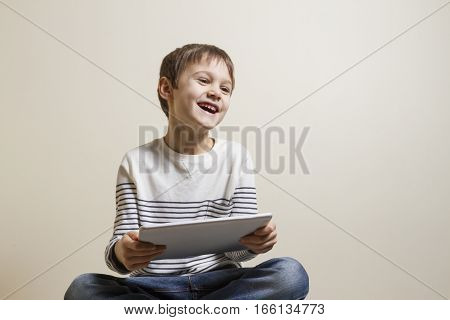 Cute playful happy child with digital tablet computer playing games. Education, learning, leisure concept