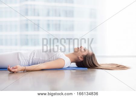Closeup side view of young attractive woman practicing yoga, lying in Savasana exercise, Dead Body, Corpse pose, working out, wearing sportswear, white t-shirt, indoor, floor window with city view