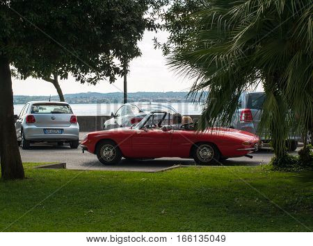 SIRMIONE, ITALY - MAY 5, 2016: Couple in vintage red cabriolet Alfa Romeo Giulietta Spider in Sirmione Garda Lake Italy