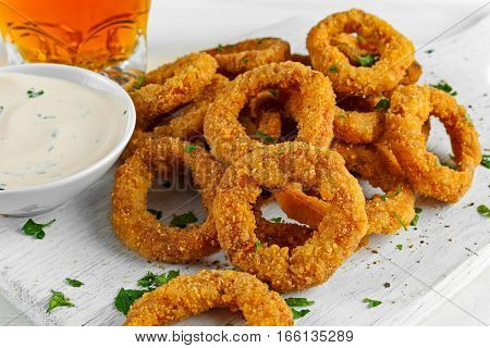 Fried Breaded Onion Rings with sauce and Light Beer on white wooden board, background.
