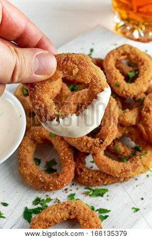 Man Holding Fried Breaded Onion Rings with sauce. on white wooden board, background