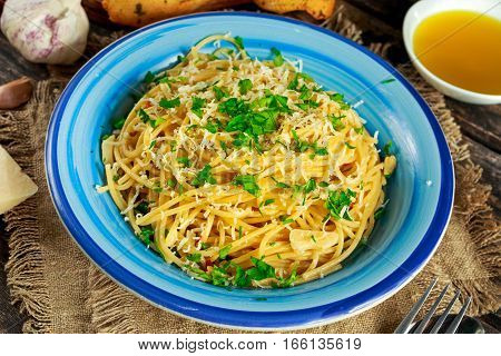 Vegetarian Italian Pasta Spaghetti Aglio E Olio with garlic bread, red chili flake, parsley, parmesan cheese and glas on water.