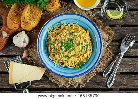 Vegetarian Italian Pasta Spaghetti Aglio E Olio with garlic bread, red chili flake, parsley, parmesan cheese and glas of water
