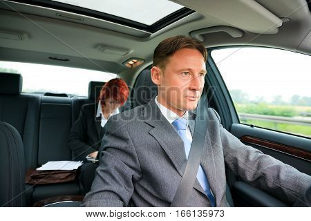 young business people on the road with him driving and her sitting in the pack, doing paperwork