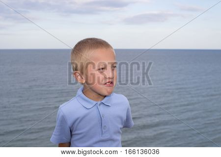 boy shows emotion on the background of the sea frowns face