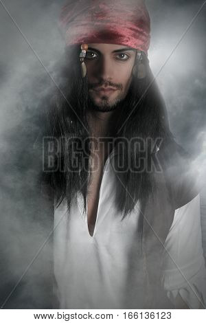 Handsome pirate posing over a smoky background