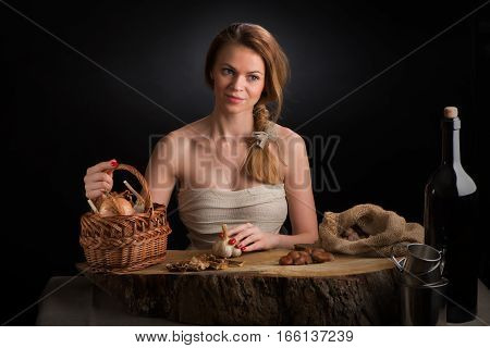 The young beautiful girl in a sundress from a canvas sits at an oak table with a garlic head in a hand near a basket with onions, dried mushrooms and a bag with chestnuts