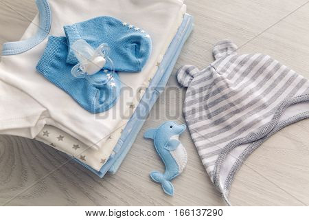 children's clothes with the diapers are stacked, and a toy dolphin