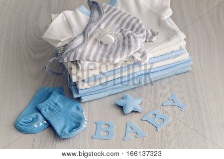 baby clothes with diapers are stacked on a wooden table with the letters baby and little star