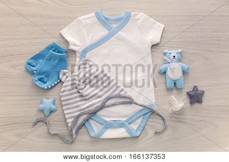 infant bodysuit with matching hat and socks lying on a white table