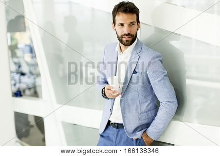Businessman With Cup Of Coffee In Office Building
