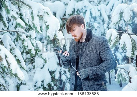 stylish man with a beard is calling on the phone in the winter forest