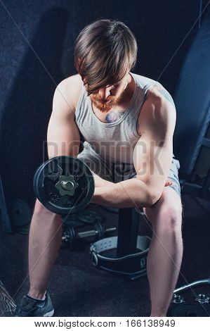 The sportsman is engaged in a gym with dumbbell