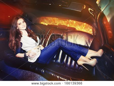 Beautiful Fashionable Young Woman In A Limousine On The Back Seat