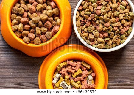 dry dog food in bowl on wooden background top view.