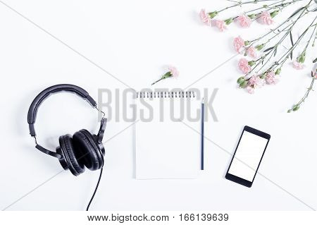 Mobile Phone, Black Headphones, Notebook, Pencil And Flowers Lie On A White Table