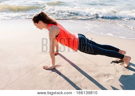 Slim girl in sportswear doing morning exercises at the beach in summer