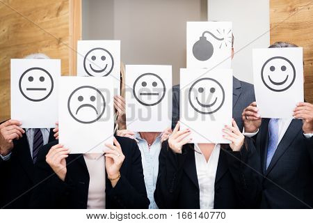 business team holding pieces of paper depicting their current emotions sad, happy or neutral . one of them feels particularly bad and is redy to explode.