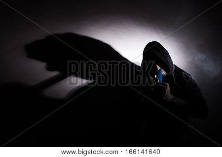 Addictive man smoking marijuana bong with a shadow on the wall