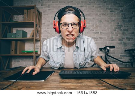 Young man with headphones and cap playing game at home and streaming playthrough or walkthrough video. Angry gamer concentrated on livestreaming in cyber world.