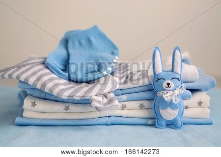children's clothes with the diapers are stacked, and a toy rabbit, hare