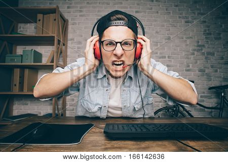 Young man playing game at home and streaming playthrough or walkthrough video. Poor guy is holding his red headphones with both hands and screaming because of fail. Looking at camera
