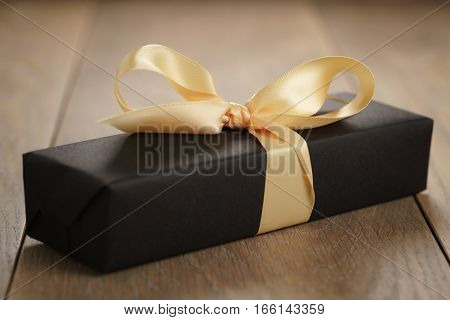 handmade gift black paper box with yellow ribbon bow on wood table, closeup photo with shallow focus