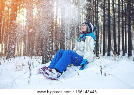 woman snowboarder with the snowboard is resting sitting on the snow among the trees on sunset background concept of sport and active lifestyle