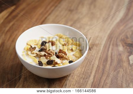 corn flakes with fruits and nuts in white bowl on wood table with copy space, healthy food