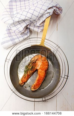 grilled salmon steak in a brass pan with thyme and oil