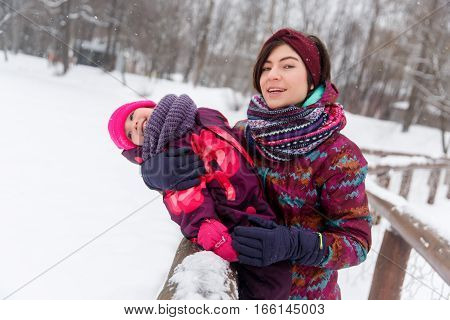 Mum embraces small daughter in winter forest
