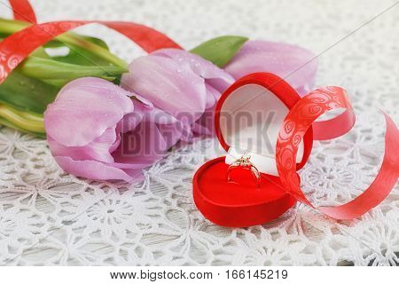 Golden engagement ring in a heart shaped box and a flower tulips
