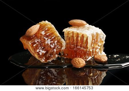 two pieces of organic honeycomb with almonds isolated on black background with reflection